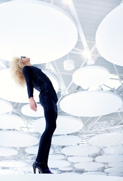 Blond futuristic vintage sexy woman in black on modern indoor full length Premium Photo