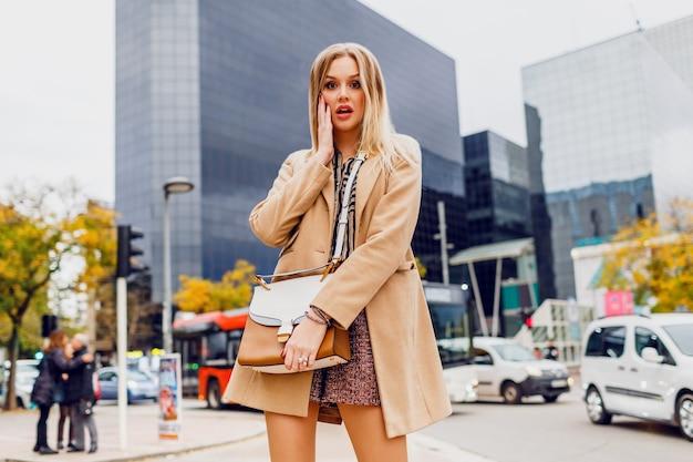 春のカジュアルな服装のブロンドの女の子が屋外を歩いて、大きな近代的な都市で休日を楽しんでいます。ウールベージュのコートと剥奪されたブラウスを着ています。スタイリッシュなアクセサリー。 無料写真