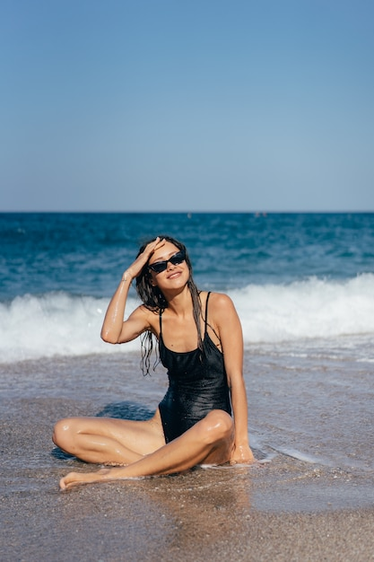Blond girl in swimsuit sitting at sea beach tanning Free Photo