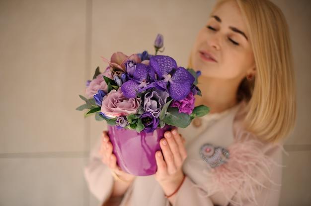 Blond girl with irises in flower pot Premium Photo