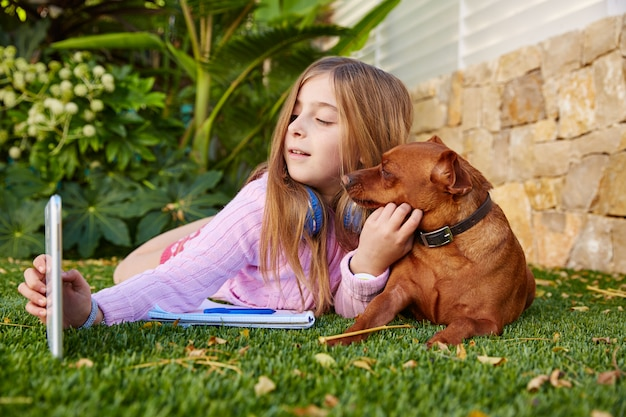 Blond kid girl selfie photo tablet pc and dog Premium Photo