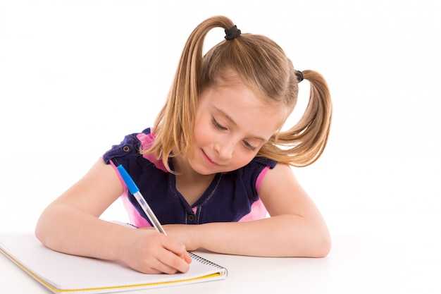 Blond kid girl student with spiral notebook in desk Premium Photo