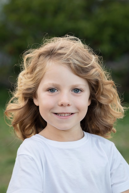 Blond kid with long hair outdoors Premium Photo