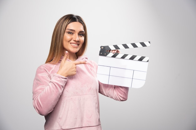 Blond lady in pink sweatshier holding a blank clapper board and gives natural poses. Free Photo
