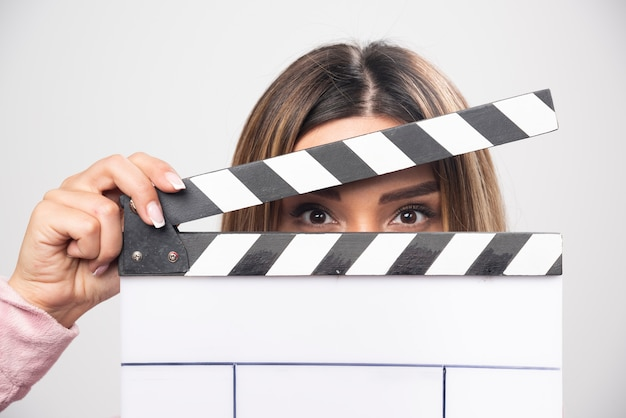 Blond lady in pink sweatshier holding a blank clapper board and looking through it. Free Photo