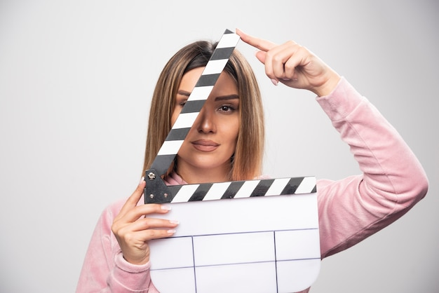 Blond lady in pink sweatshier holding a blank clapper board and looking through it Free Photo