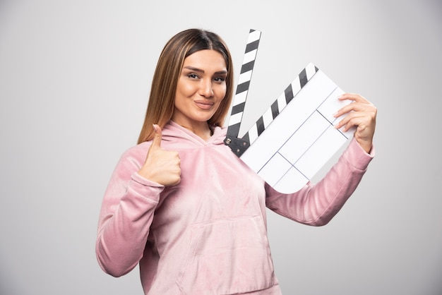 Blond lady in pink sweatshirt holding a blank clapper board and gives professional poses. Free Photo