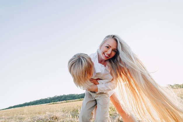 Blond little boy playing with mom with white hair with hay in field. summer, sunny weather, farming. happy childhood. Free Photo