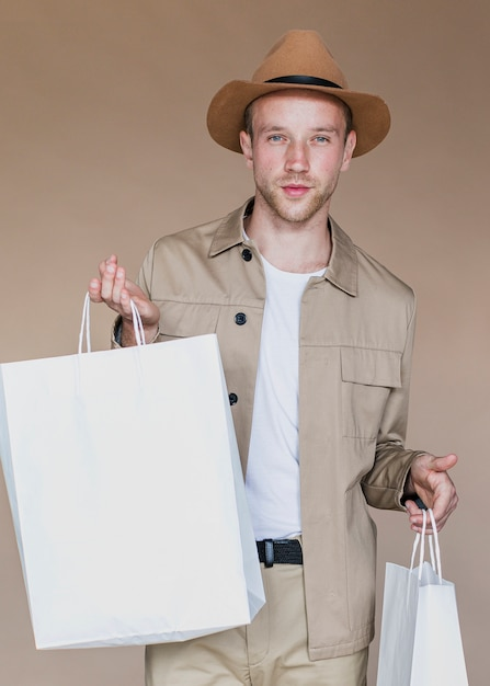 Blond man with shopping bags looking to the camera Free Photo