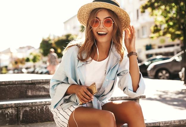 通りでポーズをとって夏服の金髪モデル 無料写真