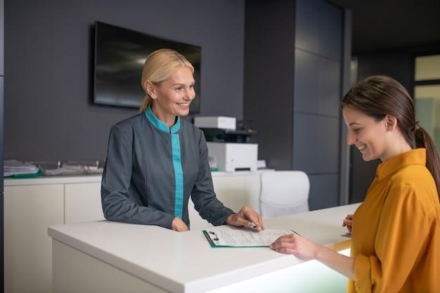 Блондинка портье в клинике разговаривает с посетителем Premium Фотографии