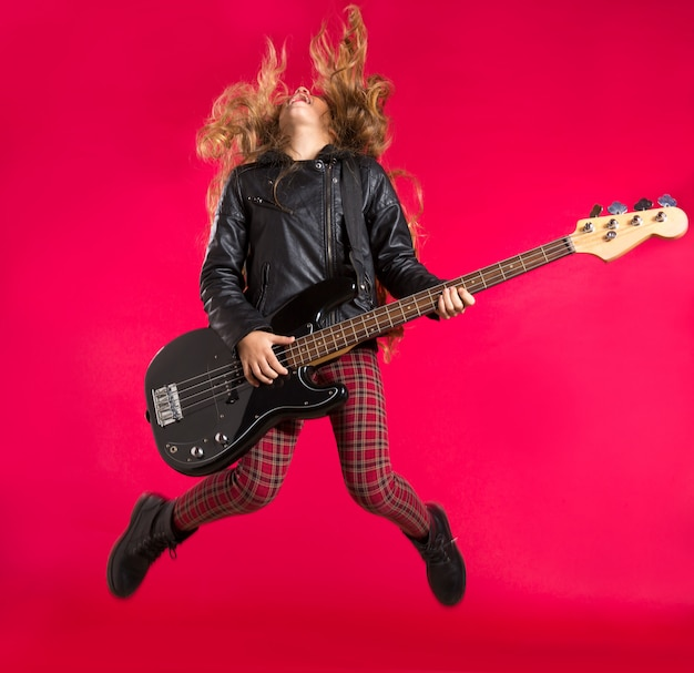 Blond rock and roll girl with bass guitar jump on red Premium Photo