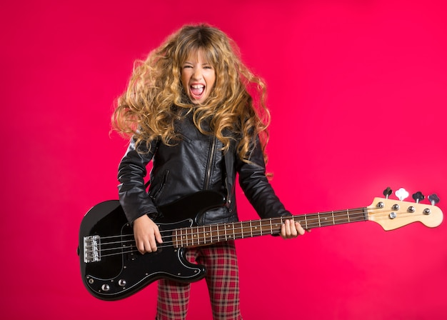 Blond rock and roll girl with bass guitar on red Premium Photo