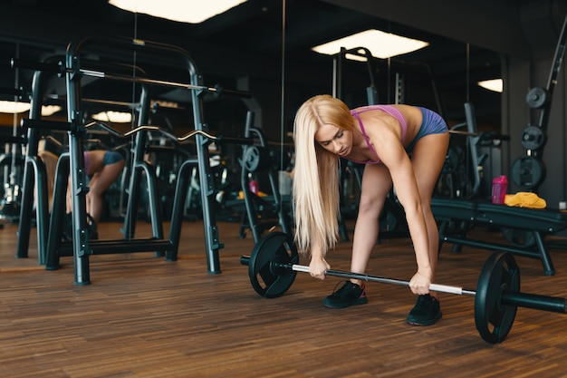 Blond sportswoman in mini shorts lifting barbell at gym workout Free Photo