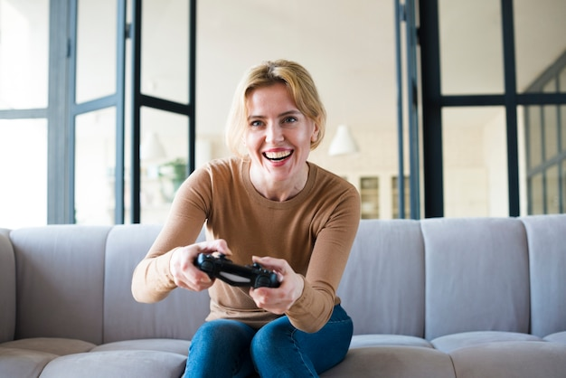 Blond woman on couch playing game console Free Photo