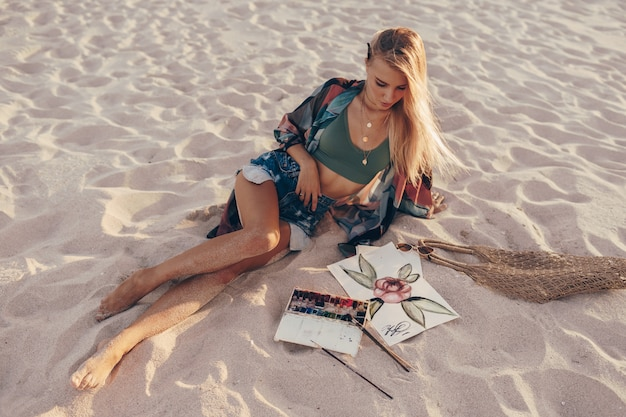 해변에서 브러시로 수채화 꽃 그리기 금발 여자 무료 사진
