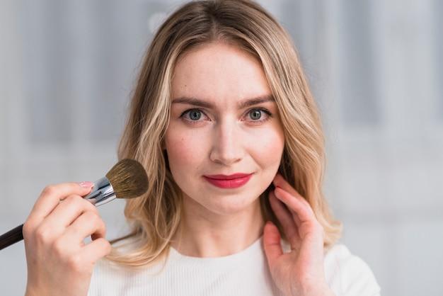 Blond woman having professional makeup Free Photo