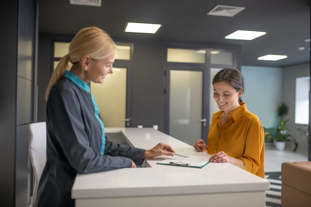 Блондинка женщина в сером пиджаке разговаривает с посетительницей Premium Фотографии