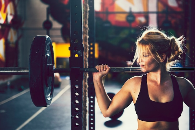 Blond woman lifting weights gym Premium Photo