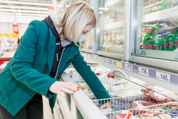 A blond woman in a medical mask chooses products in the freezing department in a supermarket. precautions during the coronavirus pandemic. Premium Photo