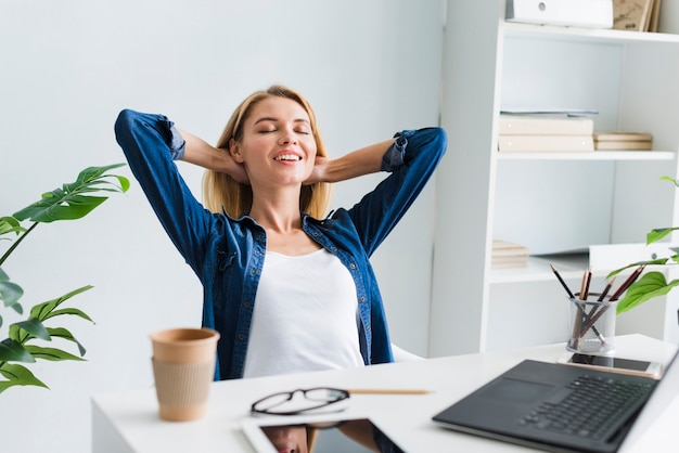 Blond woman sitting back and smiling with closed eyes at workplace Free Photo