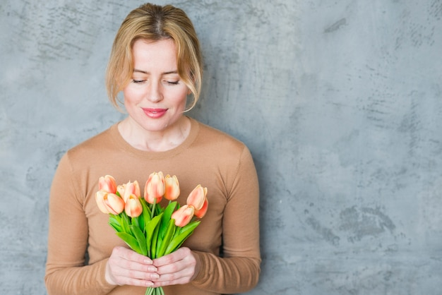 Blond woman standing with tulips bouquet Free Photo