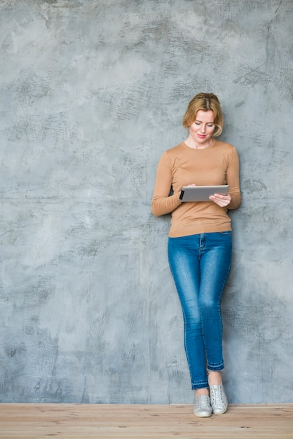 Blond woman using tablet at wall Free Photo