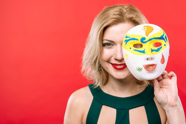 Blond woman with white carnival mask in hand Free Photo
