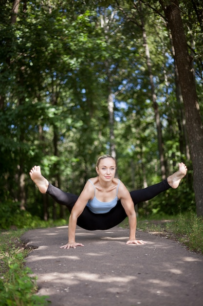 Blond young woman doing firefly yoga posture Free Photo