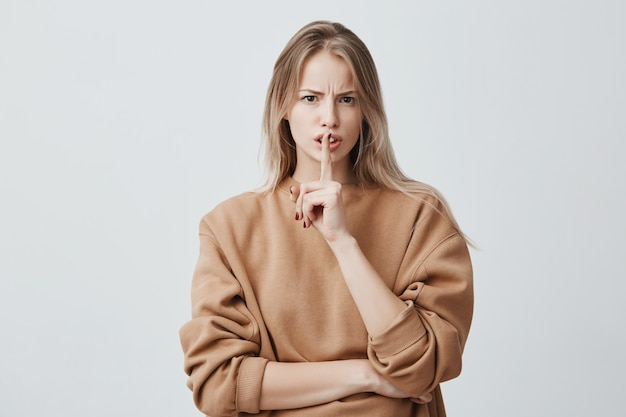 ブロンドの魅力的なヨーロッパの女性は唇に指をつけたままにしている、不機嫌で騒々しくしないように頼む 無料写真
