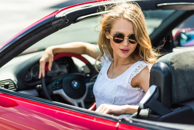 Blonde beautiful woman in sunglasses sitting in red car by the sea. sea view. vacation concept. happyness. freedom. road trip on beautiful sunny summer day Premium Photo