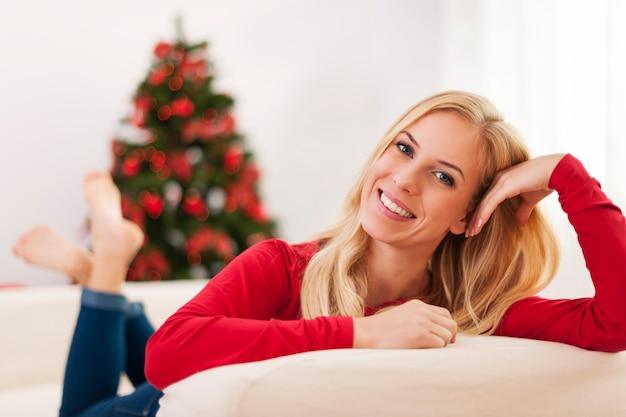 Блондинка красивая молодая женщина отдыхает на диване во время рождества Бесплатные Фотографии