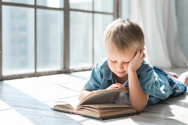 Blonde boy reading book near the window in the sunlight Free Photo