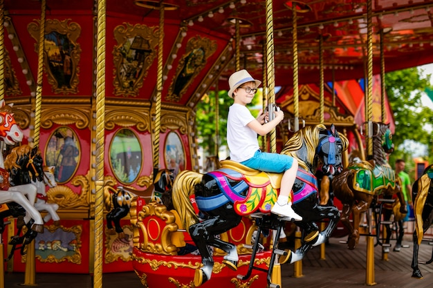 Blonde boy in the straw hat and big glasses riding colorful horse in the merry-go-round carousel. Premium Photo