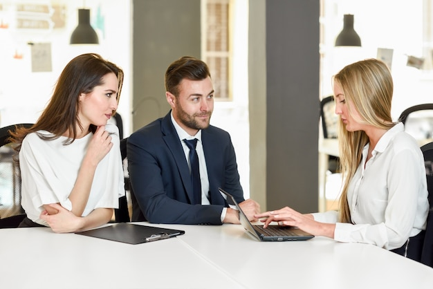 Blonde businesswoman explaining with laptop to smiling young cou Free Photo