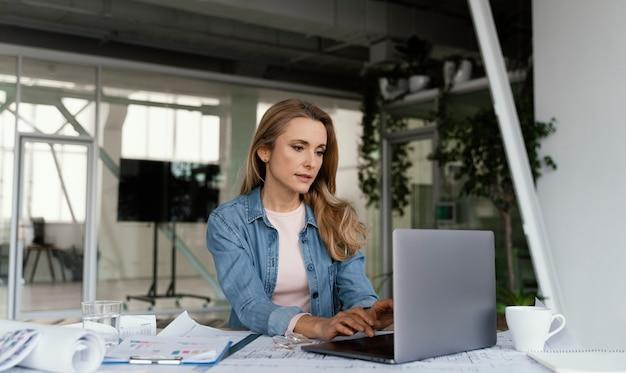 그녀의 노트북에서 일하는 금발 사업가 무료 사진