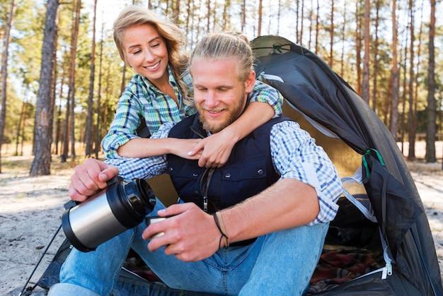 Coppia bionda seduta davanti alla tenda e bere caffè Foto Gratuite