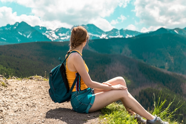 Blonde cute girl with a backpack and glasses sits on a mountain and enjoys the beautiful hills of the mountains on a sunny day. Premium Photo