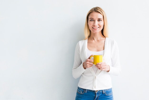 Blonde employee holding cup on white background Free Photo