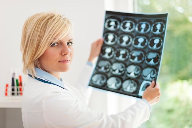 Medico femminile biondo che tiene immagine dei raggi x Foto Gratuite