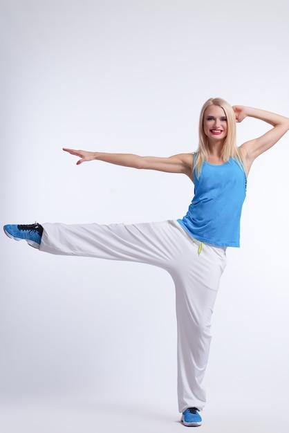 白に笑みを浮かべて片足でバランスをとるヒップホップダンスの衣装で金髪の女性 無料写真