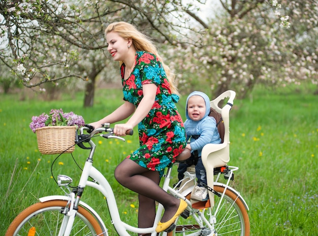 Blonde female riding city bicycle with baby in bicycle chair Premium Photo