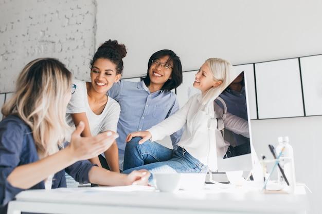 笑っている同僚に面白い話をしている金髪の女性秘書。コンピューターの横に立って、金髪の友人を聞いて笑顔のアジアのサラリーマンの屋内肖像画。 無料写真