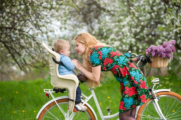 Blonde female with city bicycle with baby in bicycle chair Premium Photo