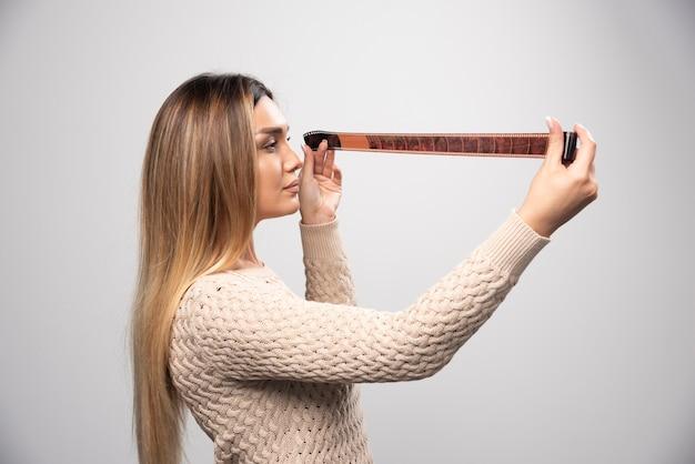 Ragazza bionda che controlla attentamente le foto sul rotolo di foto. Foto Gratuite