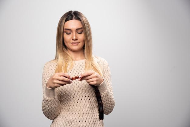 Ragazza bionda che controlla attentamente le foto su pellicola polaroid Foto Gratuite