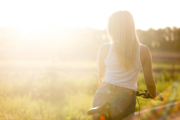 Blonde girl back riding a bike Premium Photo