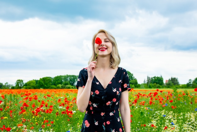 Blonde girl in beautiful dress in poppies field in summer time Premium Photo