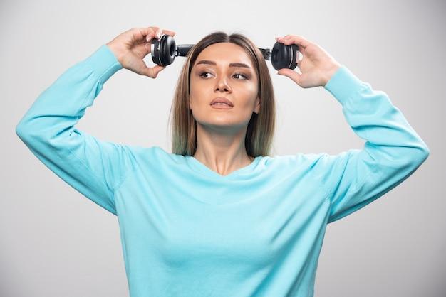 Ragazza bionda in felpa blu che tiene le cuffie e si prepara a indossarle per ascoltare la musica. Foto Gratuite