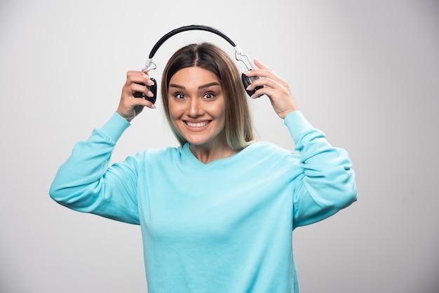 Ragazza bionda in felpa blu che tiene le cuffie e si prepara a indossarle per ascoltare la musica Foto Gratuite